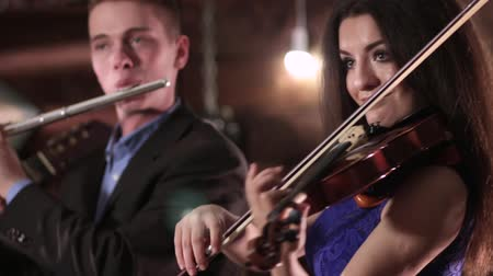flutist : Two people musician playing music. A beautiful brunette in a blue dress is playing the violin, and the guy in the jacket and the shirt on the flute. Stock Footage