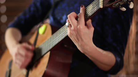 gitáros : A girl in a blue dress is playing an acoustic guitar. Close-up. Hands on the strings of a musical instrument. Defocus at the end of the video.