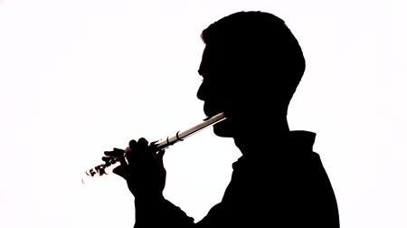 flet : Isolated silhouette of a guy playing the flute. Black and white footage. Wideo