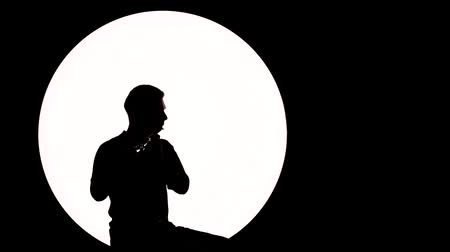 flet : Silhouette of a guy-musician. A young man plays the flute while sitting on a white background.