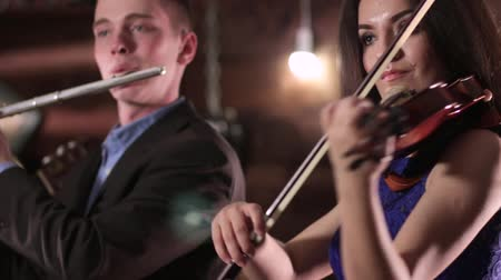 flutist : A beautiful brunette in a blue dress is playing the violin, and the guy in the jacket and the shirt on the flute. Two people musician playing music. Stock Footage