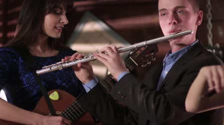 flet : Two people musician reproduce music. A guy in a jacket and shirt playing the flute, and a beautiful brunette in a blue dress playing a guitar.