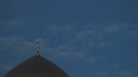 félhold : Noise and grain as on an old film. The top of the golden minaret of the mosque with a crescent is a symbol of Islam against a blue sky with clouds. Accelerated video. Left on the frame.