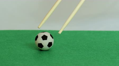 leisureactivity : Chopsticks for Chinese food raise the ball. Close-up of a soccer ball on a green felt background. Shallow depth of field.