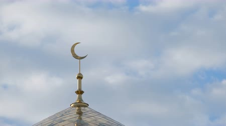 hilâl : Time Lapse. The golden crescent on the minaret of the Islamic mosque on a heavenly blue background with white clouds. Close up.