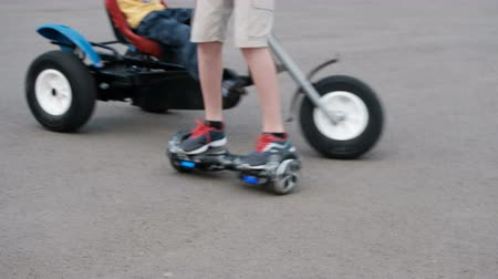 two wheeled : Blurry. The legs are close-up. Children ride a bicycle and on the hoverboard on the pavement.