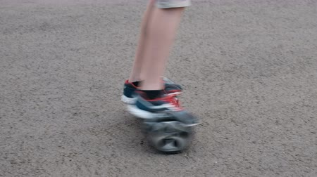 gyroscope : The teenager rides on a self-balancing two-wheeled hoverboard in a circle. Movement on the asphalt. Life style. The legs are close-up.