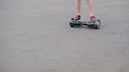 electro : The teenager rides on a self-balancing two-wheeled hoverboard on the asphalt. Movement from the right upper corner to the bottom left of the frame. The legs are close-up. Stock Footage