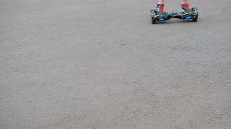 two wheeled : The teenager rides on a self-balancing two-wheeled hoverboard on the asphalt. The legs are close-up. Movement from the upper left corner to the bottom right of the frame.