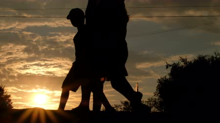 iluminado para trás : City life at sunset. Silhouette. The boy and his parents walk along the sidewalk past the roadway.