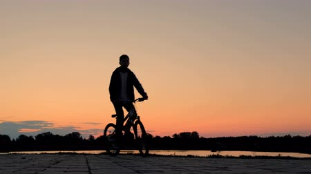 バイクに乗る人 : Silhouette of a bicyclist. The teenager rides a bicycle along the embankment. Sports lifestyle.