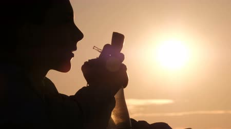 ações : The teenager opens the lid on the bottle. Silhouette of a young man against the background of the morning sun.