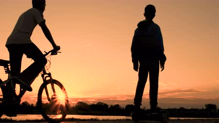 self balancing : Silhouette of teenagers at sunrise. One boy rides on a self-balancing two-wheeled gyroscope and another young man on a bicycle. Stock Footage