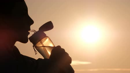 humanóide : Silhouette of a teenager profile against the sun. The guy opens a sports bottle and drinks. Backlighting. Copy space.