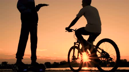 self balancing : Silhouette of teenagers at sunrise or sunset. One boy rides on a self-balancing two-wheeled gyroscope, and another young man on a bicycle on the river embankment.