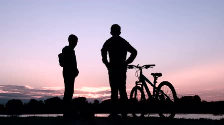 self balancing : Silhouette of two teenagers communicating on the river bank or lake. Young people meet at sunrise or sunset on a bicycle and gyro. Handshake of friends. Stock Footage