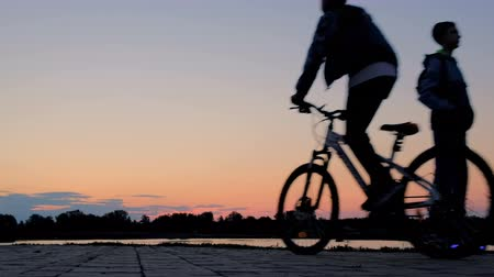 gyro : A teenager on a two-wheeled self-balancing hoverboard and a guy on a bicycle ride past each other near the pond along the embankment at dawn. Sports lifestyle. Silhouette of the boys in the morning light.