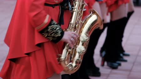 saxofon : The brass band Kostanay. Girls in hussar red clothes and black boots play saxophones. Close-up.
