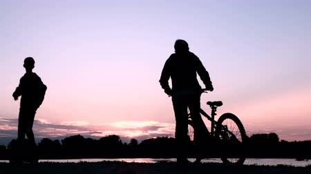 self balancing : Two young people shake hands with each other and say goodbye. One teenager leaves on a bicycle, and another guy on a two-wheel gyroscope. Silhouettes of people at sunrise or sunset. Stock Footage