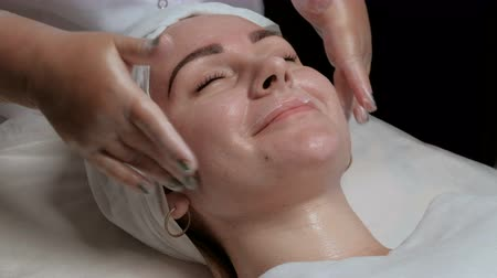 soyulması : Wooman in beauty salon. The cosmetologist in transparent gloves, the cream and massages on the forehead, cheeks and chin of the clients face Stok Video