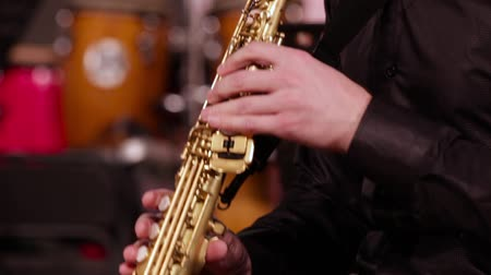 chave : A man in a black shirt plays jazz music. Close-up of the hands of a saxophonist on a soprano saxophone.