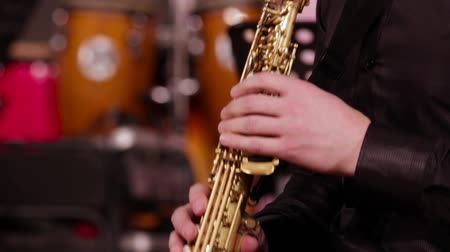 saxofon : Close-up of the hands of a saxophonist on a soprano saxophone. A musician in a black shirt. Jazz concert.