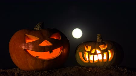 сквош : Two pumpkins with candles inside. Time laps. Night sky, full moon. Holiday Halloween.