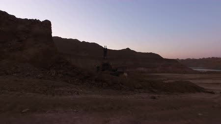 opencast : Extraction of minerals in open-pit quarry. Eksakvator loads rock into the truck. Evening photography. Move the video operator forward. Stock Footage