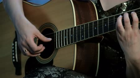 gitáros : Close-up of the hands of a girl playing an acoustic guitar. Focus on the fingers clamping the chords on the fretboard. Day of music. Stock mozgókép