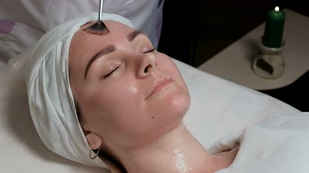 soyulması : A professional beautician makes a last brushstroke on the girls forehead. The procedure for applying a transparent gel with a brush on the face of the client in the beauty salon. A candle burns.