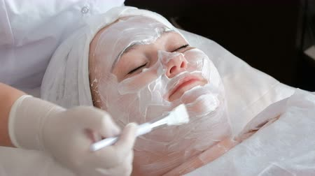 bil : A fat woman receives a procedure of cleaning and lifting the face skin in the beauty salons office. The hands of the cosmetologist in gloves smear with a brush a white cream on the forehead of a girl