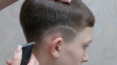 střih : A modern teenage hairstyle in a barber shop. A close-up of the hands of a hairdresser who shaves a strip over the ear of a young man with a hair clipper.