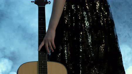 akusztikus : A girl in an evening dress approaches an acoustic guitar and runs her hand along the strings from the bottom up. Smoke in the background. Day of music.