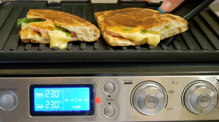 cheddar : The girl removes ready-made sandwiches from the stove. Cooking on an electric grill. Quick hot breakfast. Stock Footage