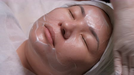 tatar : A professional beautician applies to an Asian girl. Womens skin rejuvenation procedure in a beauty salon. Close-up. Wideo