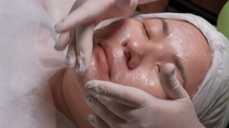 tatar : Close-up. East girl on the procedure of cleansing of the skin in the beauty salon. The hands of a professional beautician in gloves put white cream on the face of a Muslim woman with her eyes closed. Wideo