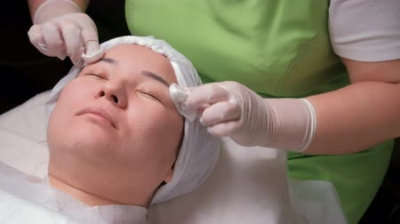 tatar : Beautician in green dress girl with cotton pads. Beauty is a woman during a rejuvenating skin procedure. Womens hands in white gloves. Wideo