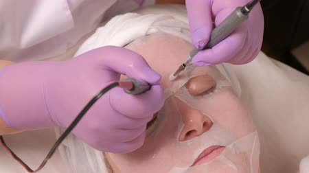 microdermabrasion : Close-up of professional beautician hands touching female forehead with Microcurrents. Cosmetology and beauty concept. Spa treatment receiving stimulating electric facial from therapist.