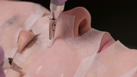 clamp : Microcurrent therapy. A professional cosmetologist smoothes wrinkles on the girls cheek. Close-up. Beauty salon.