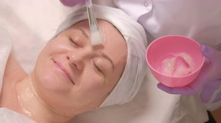 clamp : Beautician smearing hair with a cream. The procedure for the skin is in the beauty center.