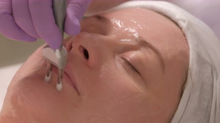 braçadeira : Cosmetic procedure for facial massage using an electric apparatus. Close-up of cosmetologists hands in gloves