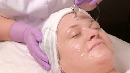 clamp : Spa clinic receiving stimulating electric facial therapia. Close-up of professional beautician hands touching female forehead with Microcurrents. Cosmetology and beauty concept. Stock Footage