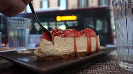 saborear : eat a slice of strawberry cheesecake with a street of Rome in the background