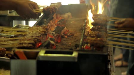 grelha : Street vendors in Singapore grilling meat Satay over charcoal barbecue pit with open flames Vídeos
