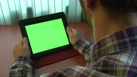 érintőképernyő : Man using digital tablet with a green screen to add your own custom content (and alpha matte)