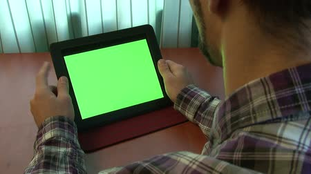 жест : Man using digital tablet with a green screen to add your own custom content (and alpha matte)
