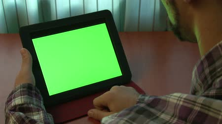 érintőképernyő : Man using digital tablet with a green screen to add your own custom content Stock mozgókép