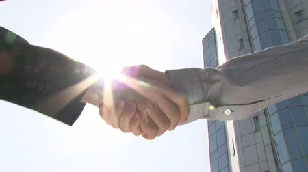 сильный : Two businessmen shaking hands in front of office building