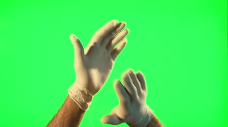 latex gloves : Male hands with surgical gloves clapping on green screen