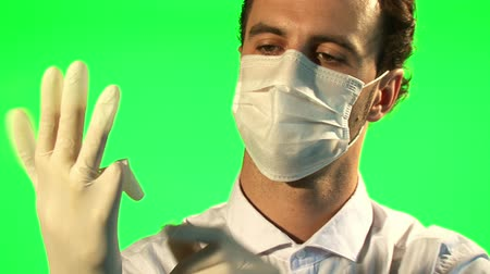 cerrahi : Doctor puts on mask and surgical gloves - green screen